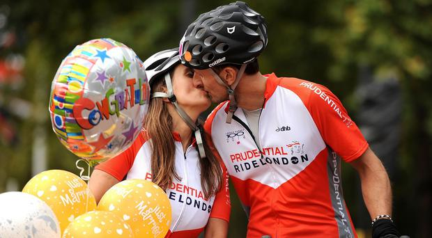 Newlyweds Gary Watson and Lisa Russell kiss after they tied the knot en-route in the Prudential RideLondon-Surrey 100.