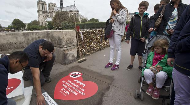 City workers fix a sticker on the pavement of Paris's Pont de l'Archeveche asking people to take selfies rather than attach a padlock to the bridge (AP)