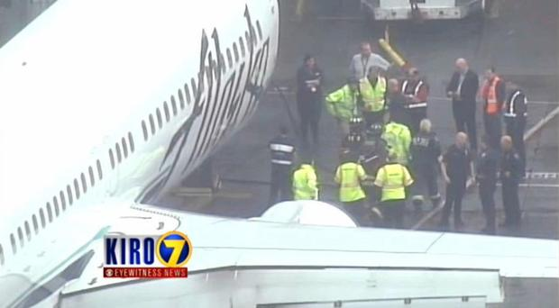 In this frame from video, workers walk with a Menzies Aviation cargo worker who was removed from the cargo hold of an Alaska Airlines passenger plane (AP/KIRO 7)