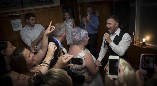 Gary Barlow serenades lifelong Take That fan Katie Hardy on her wedding day at the Three Nuns pub in Loughborough (David Moody/PA)