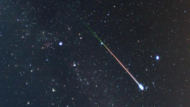 The stars of the constellation of Cygnus are visible on the left of the shooting star