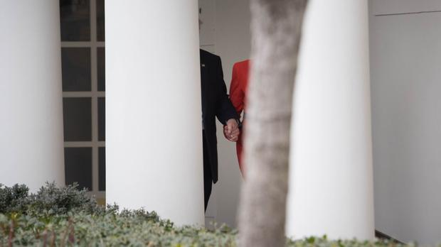 US President Donald Trump and Prime Minister Theresa May holding hands as they walk along the White House Colonnade during her visit to Washington