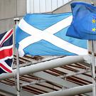 A Union Jack, Saltire and European flag fly outside the Scottish Parliament, Edinburgh.
