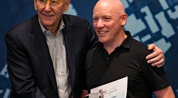 Jack Dangermond (left), Esri president, presents Sean O'Boyle, asset information development manager, NI Water, with a Special Achievement in GIS (SAG) Award
