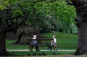 People keeping their distance talk on a bench in a park in London