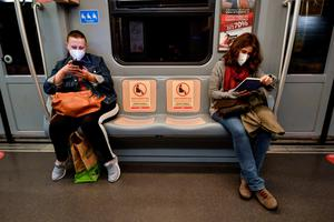 Women on a subway train in Milan with seat signs reading 'Please do not sit here, respect social distances'