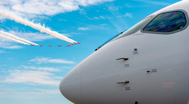 The Red Arrows flying past an Airbus 220 on display at the Farnborough Airshow