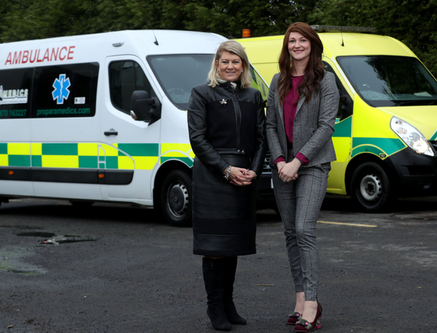 Heather and Megan with two of the firm's ambulances
