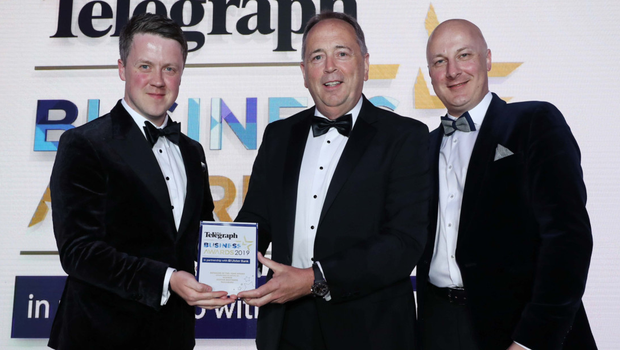 Retail NI president Peter McBride (centre) presents last year's Retailer of the Year award to William and Chris Suitor from Suitor Brothers Tailoring