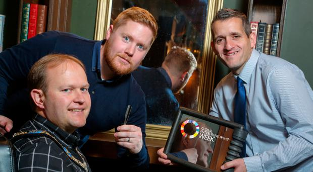 Entrepreneur Dwaine Smyth (centre) in one of his The Elk & Clipper barbershops with Lord Mayor Gareth Wilson (left) and Paul Reid, business development manager from principal sponsor Ulster Bank