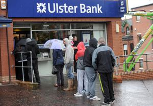 Long wait: Customers queue at an Ulster Bank branch in Belfast during the crisis