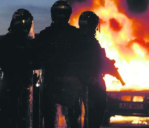 Riot police stand next to a burned out car after Loyalist protesters attacked police lines, in east Belfast. PRESS ASSOCIATION Photo. Picture date: Saturday January 12, 2013. See PA story ULSTER Protests. Photo credit should read: Paul Faith/PA Wire