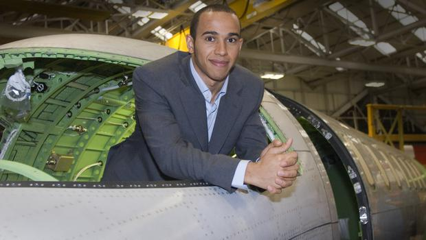 Formula One champion Lewis Hamilton checks out a plane during a visit to Bombardier in Belfast