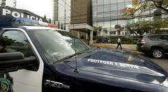 A police car stands outside the Mossack Fonseca law firm while organised crime prosecutors raid the offices (AP)