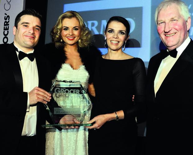 Ryan McFarland, of Bacardi Brown-Forman Brands, and Miss NI Tiffany Brien present Premier Bakeries' Jackie Kirk with the award for Best Marketing Campaign, along with Ulster Grocer publisher James Greer