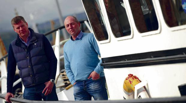 Alan McCulla (left) and David Hill in a boat in Kilkeel harbour as they bid to transform the town