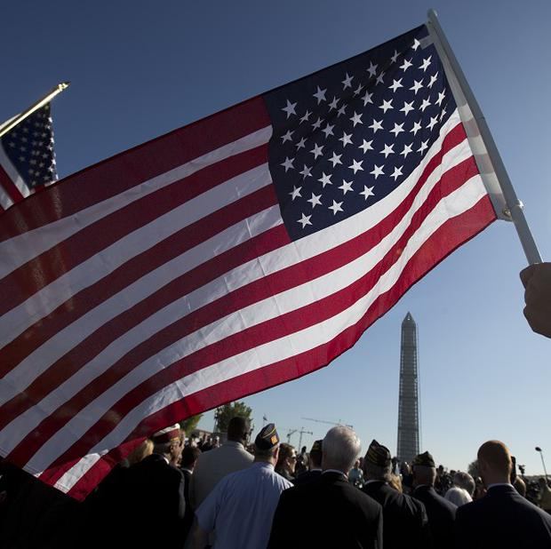 US Marine Terri Shreiner holds an American flag during a rally at the National World War II Memorial in Washington, by the Military Coalition, which is demanding an end to the partial US government shutdown.