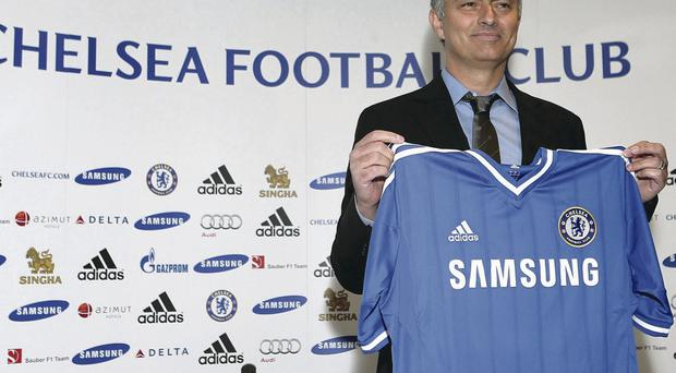 Chelsea manager Jose Mourinho holds up the club shirt