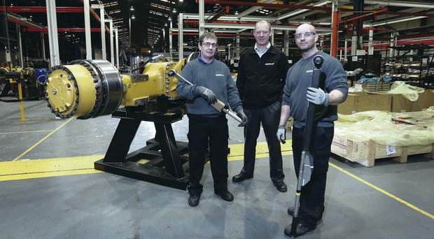 Caterpillar NI operations director Robert Kennedy in front of one of the axles the company will be producing in Northern Ireland, with Jackie Glenn and Darryl Parke, who are involved in assembling the products