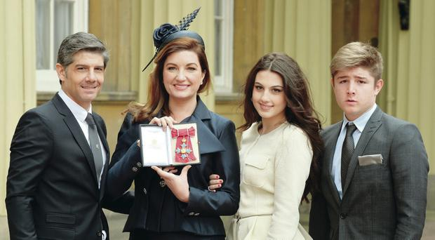 Karren Brady holds her CBE, as she poses with her husband Paul Peschisolido and children Sophia and Paolo