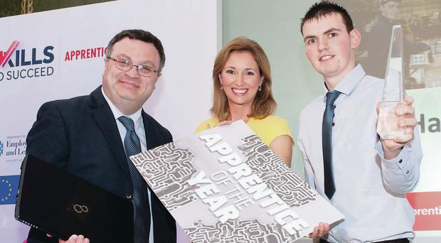 Apprentice of the Year Gareth Harkness is congratulated by Employment Minister Dr Stephen Farry and awards ceremony host Claire McCollum