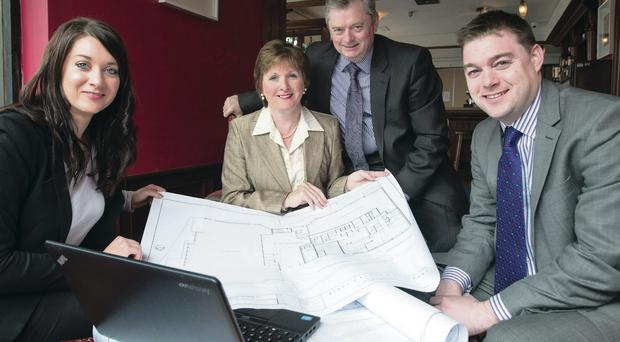 Eugene and Catherine McKeever of McKeever Hotel Group look over the plans for their new hotel with daughter Bridgene and son Eddie