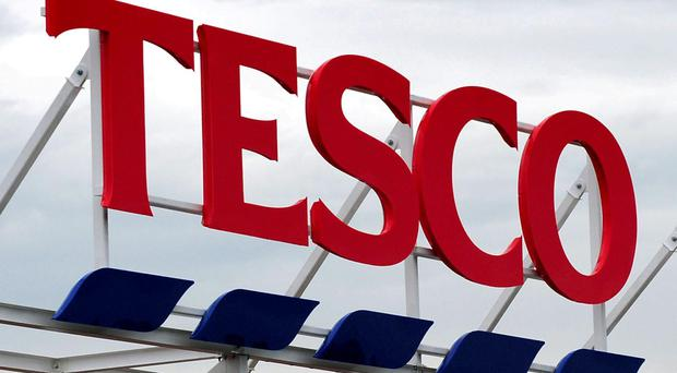 File photo dated 01/08/12 of a Tesco sign, as the supermarket issued another warning on profits and said it will cut its half-year dividend for shareholders by 75%. New chief executive Dave Lewis will now join the company on Monday - a month earlier than planned. PRESS ASSOCIATION Photo. Issue date: Friday August 29, 2014. See PA story CITY Tesco. Photo credit should read: Rui Vieira/PA Wire