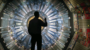 A visitor taking a photograph of a large backlit image of the Large Hadron Collider (LHC) at the Science Museum's Collider exhibition. PuppetLabs looks after the IT infrastructure for the colossal machine in Geneva