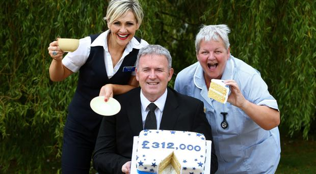 Donna Cochrane (left) and Stephen Cruise from Ulster Bank celebrate a record-breaking One Week in June charity fundraising campaign with Marie Curie nurse Laurie Lancaster (right)