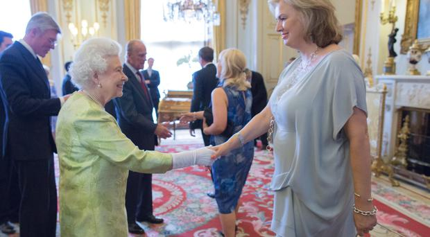 Vita Liberata chief executive Alyson Hogg is congratulated by the Queen in Buckingham Palace after winning her award