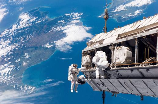 Astronauts during a space walk on the International Space Station with New Zealand in the background