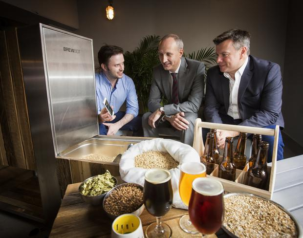 Chris McClelland, chief executive of Brewbot, demonstrates his technology to Ian Sheppard from Bank of Ireland and Steve Orr of NISP CONNECT at the publication of the 2015 Knowledge Economy Report
