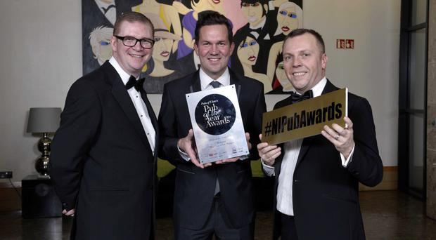 Finance Minister Simon Hamilton, Andrew Gedge from The Goat's Toe, Bangor, with the 2014 Pub of the year award, and Pubs of Ulster chairman Mark Stewart