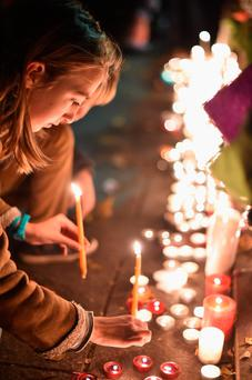 A young girl lights a candle opposite the Bataclan concert hall