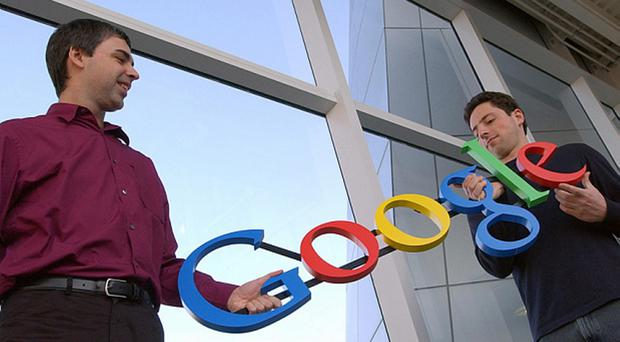 From left, Google founders Larry Page and Sergey Brin, with a model of the company's original logo