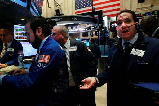 Traders on the floor of the New York Stock Exchange yesterday as oil prices fell to their lowest since 2005, affecting the cost of petrol and home heating oil here
