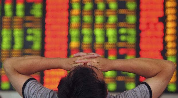 A forlorn Chinese investor gestures in front of an electronic board showing stock information at a brokerage earlier this month
