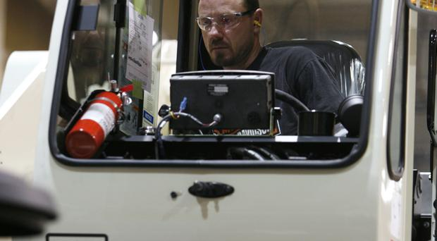 A worker inspects a crane on the assembly line at a Terex Corporation plant