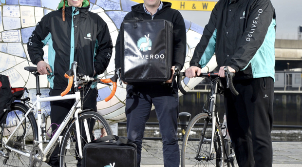 Rider Michael Dryer, Deliveroo general manager of Ireland Oliver Dewhurst and Rider Andrew Reid celebrate company's launch in Belfast