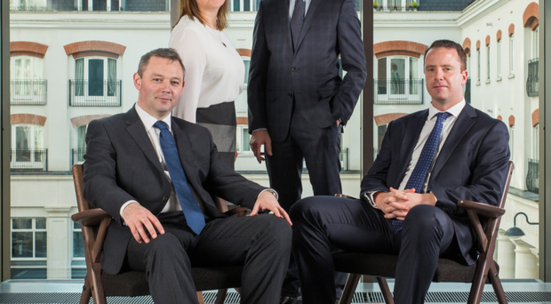 Tughans corporate team: John-George Willis (right, standing) with Ciara Lagan, John McGuckian (front right) and James Donnelly