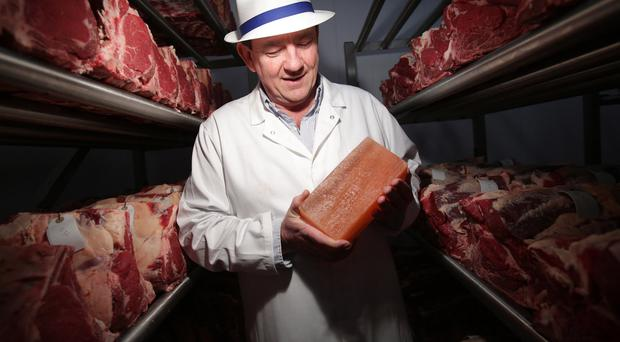 Peter in the dry age storage unit which uses blocks of Himalayan salt built in a wall to help cure the meat
