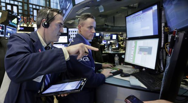 Trader Gregory Rowe, left, works on the floor of the New York Stock Exchange (AP)