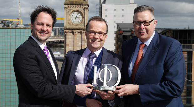 Richard Ennis of sponsors First Trust Bank and Paul Terrington, chairman of the IoD NI, present Colin Coffey of Flint Studios (centre) with the non-executive Director of the Year award, sponsored by Invest Northern Ireland, at the 2016 IoD NI First Trust Bank Director of the Year Awards ceremony