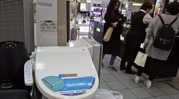 Shoppers stand near a smart toilet seat cover on display in Beijing, China (AP)