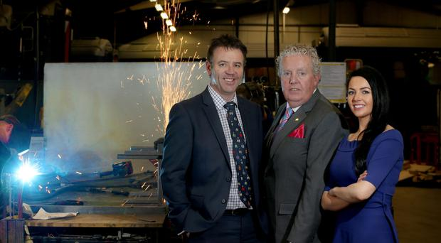Belfast Telegraph Businessperson of the Year Brian McConville (centre), group chairman of MJM Group, with the group's chief executive Jarlath Quinn and group executive assistant Naoimh McConville