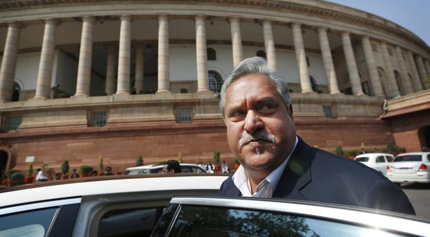 Vijay Mallya gets into his car outside the Parliament in New Delhi (AP)