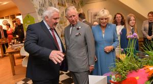 Simon Dougan shows Prince Charles and the Duchess of Cornwall on their visit to The Yellow Door in Portadown