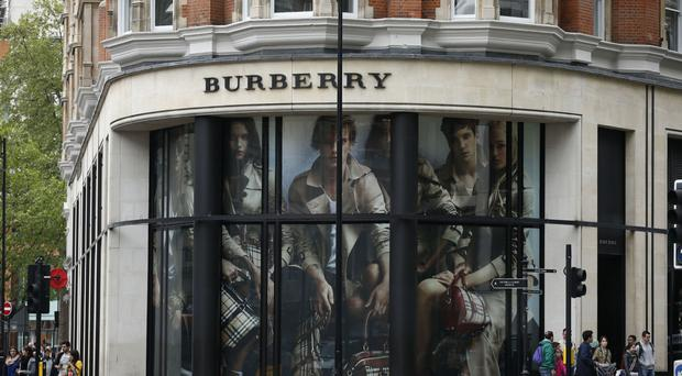 The boss of Burberry has seen his pay slashed as the company struggles with slower growth