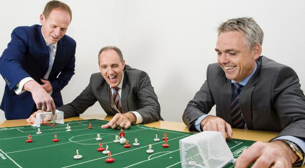 From left, Gavin Campbell of Barclays, Tom Picking of WIS and Glenn Roberts from Deloitte get into the Euros spirit with a game of Subbuteo