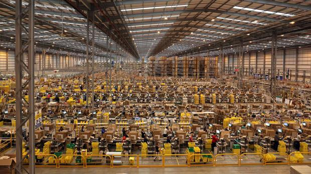 Workers pack orders on the warehouse floor at the Amazon UK Fulfilment Centre in Peterborough, Cambridgeshire